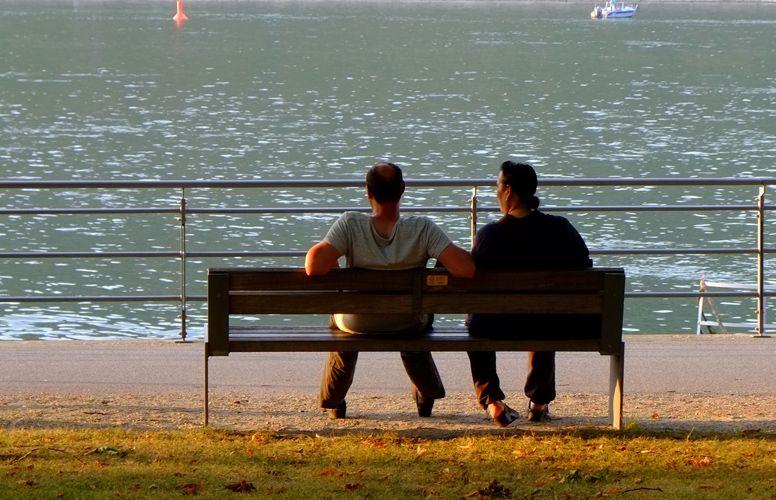 deux hommes parlent sur un banc